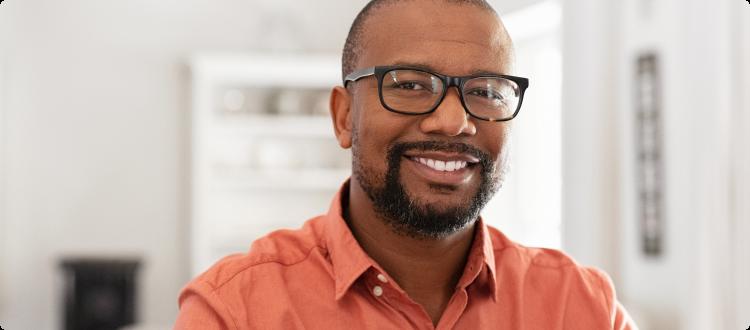 Na imagem, lê-se: três Homem negro usando óculos de grau, sorrindo e olhando para câmera.