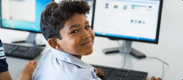 Na imagem, lê-se: criança olhando para a câmera e sorrindo enquanto usa o computador.
