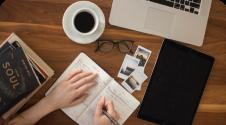 imagem de duas mãos sobre um caderno representando educação e estudo