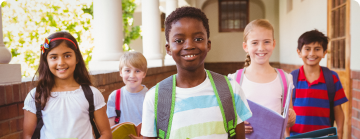Na imagem, lê-se: cinco crianças com mochilas caminhando em direção a sala de aula