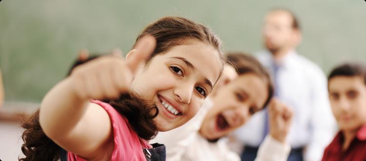 Na imagem, lê-se: três crianças, duas ao fundo desfocada e uma na frente olhando para a câmera sorrindo e fazendo gesto de joinha.