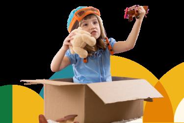 Na imagem, lê-se: Criança com adereço na cabeça, dentro de uma caixa de papelão brincando com avião e urso de pelúcia.