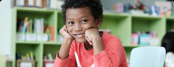 Na imagem, lê-se: Criança negra segurando apoiando o rosto sobre as mãos.