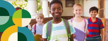 Na imagem, lê-se: quatro crianças com mochilas sorrindo e caminhando em direção a sala.