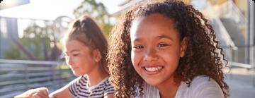 Na imagem, lê-se: duas crianças, uma negra e outra orietal, sorrindo.