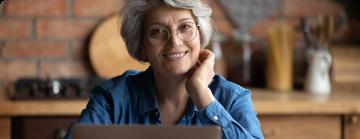 Na imagem, lê-se: senhora de cabelos grisalho usando oculos e com o rosto apoioado sobre a mão esquerda.