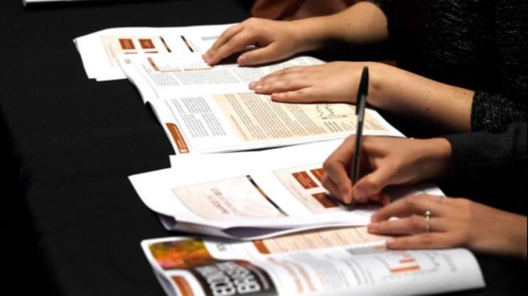 Pessoa fazendo anotações em folhas de papel de pesquisas divulgadas pela CNI