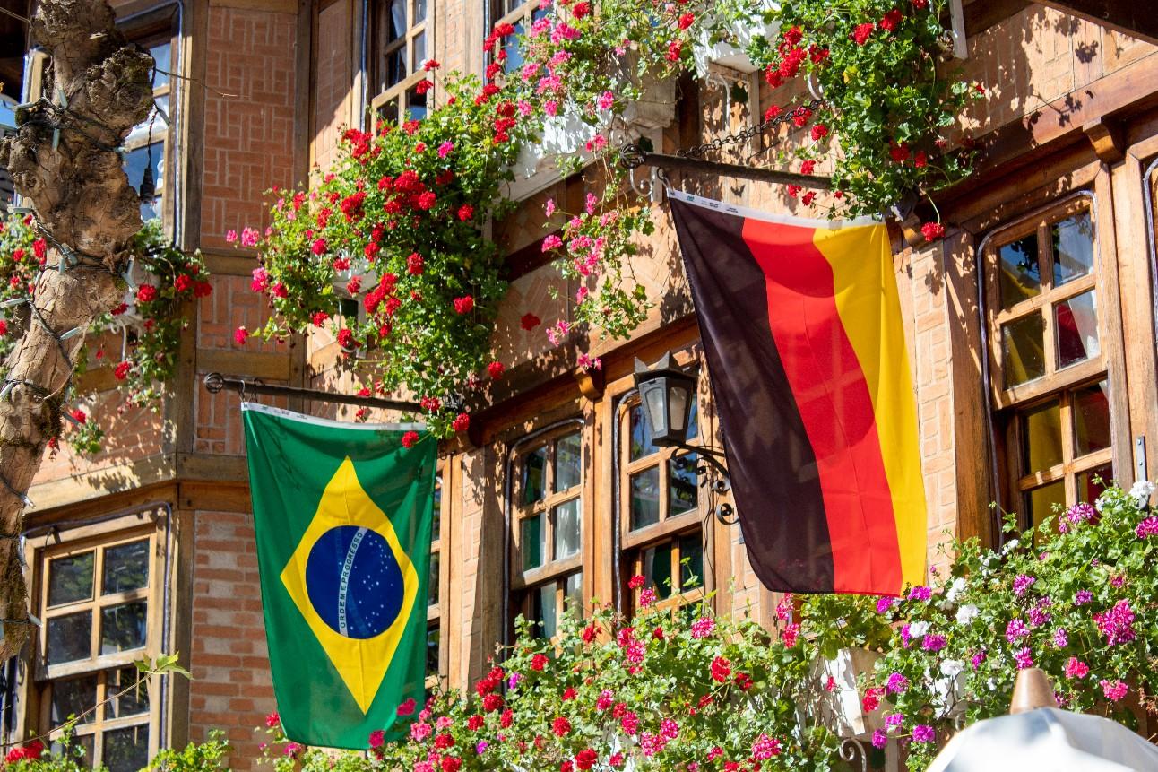 Bandeiras do Brasil e Alemanha na sacada de um prédio com flores