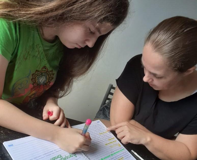 Foto: mãe e filha fazendo atividade no caderno