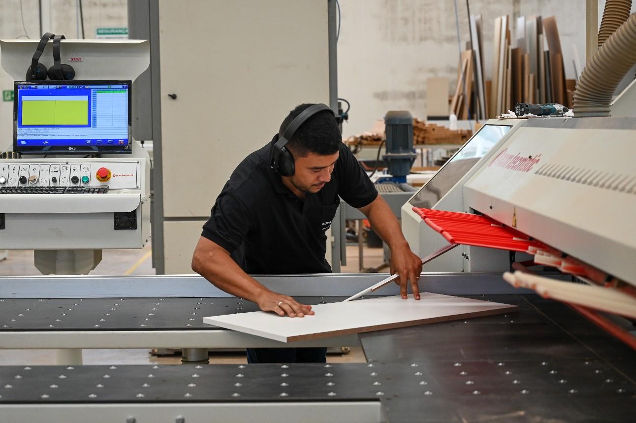Trabalhador operando uma máquina de fabricação de móveis de madeira