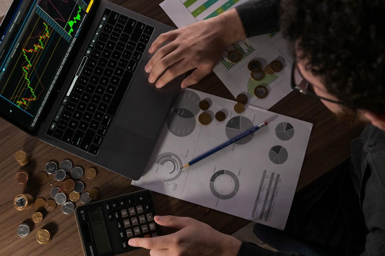 Homem utilizando planilha, calculadora e computador calcula receitas e despesas