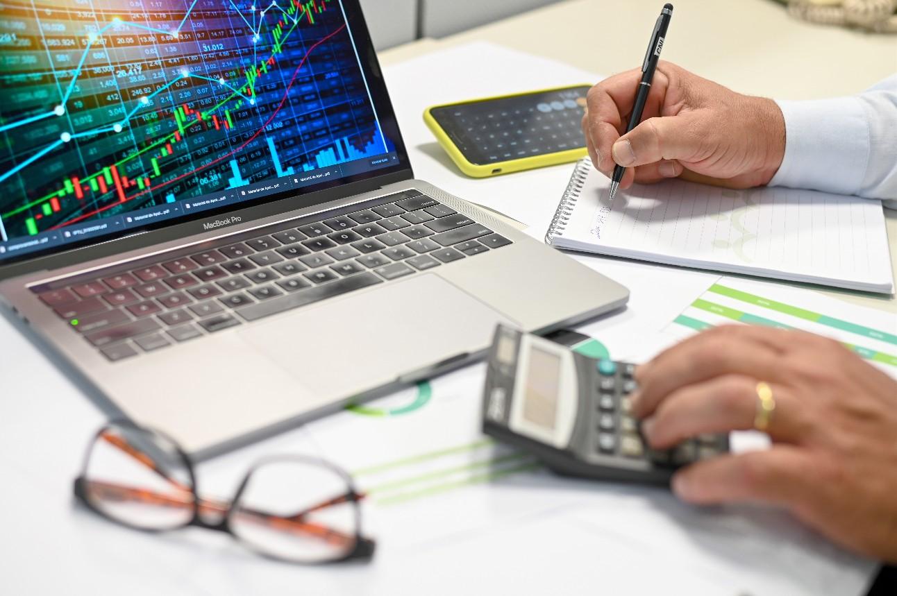 Mãos de um homem utilizando calculadora e fazendo anotações, com um notebook ao fundo mostrando um gráfico de crescimento