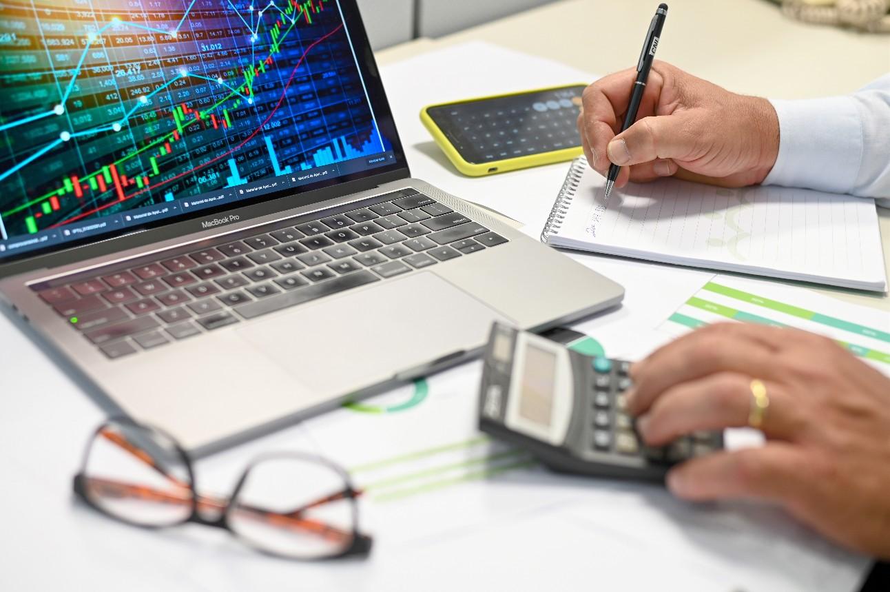 Homem fazendo anotações e digitando em calculadora, com gráficos na tela de um notebook