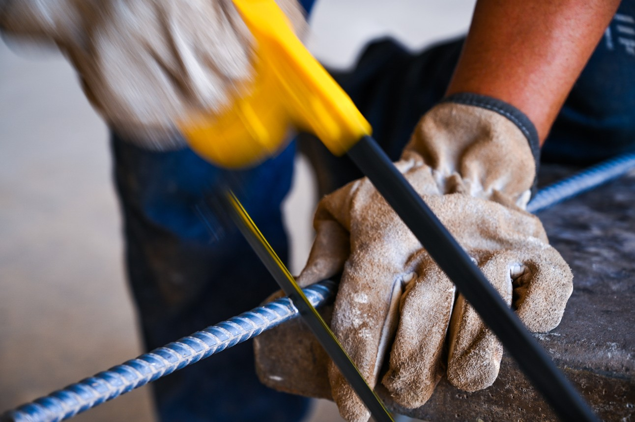 Foto mostra mãos de trabalhador serrando um vergalhão em obra
