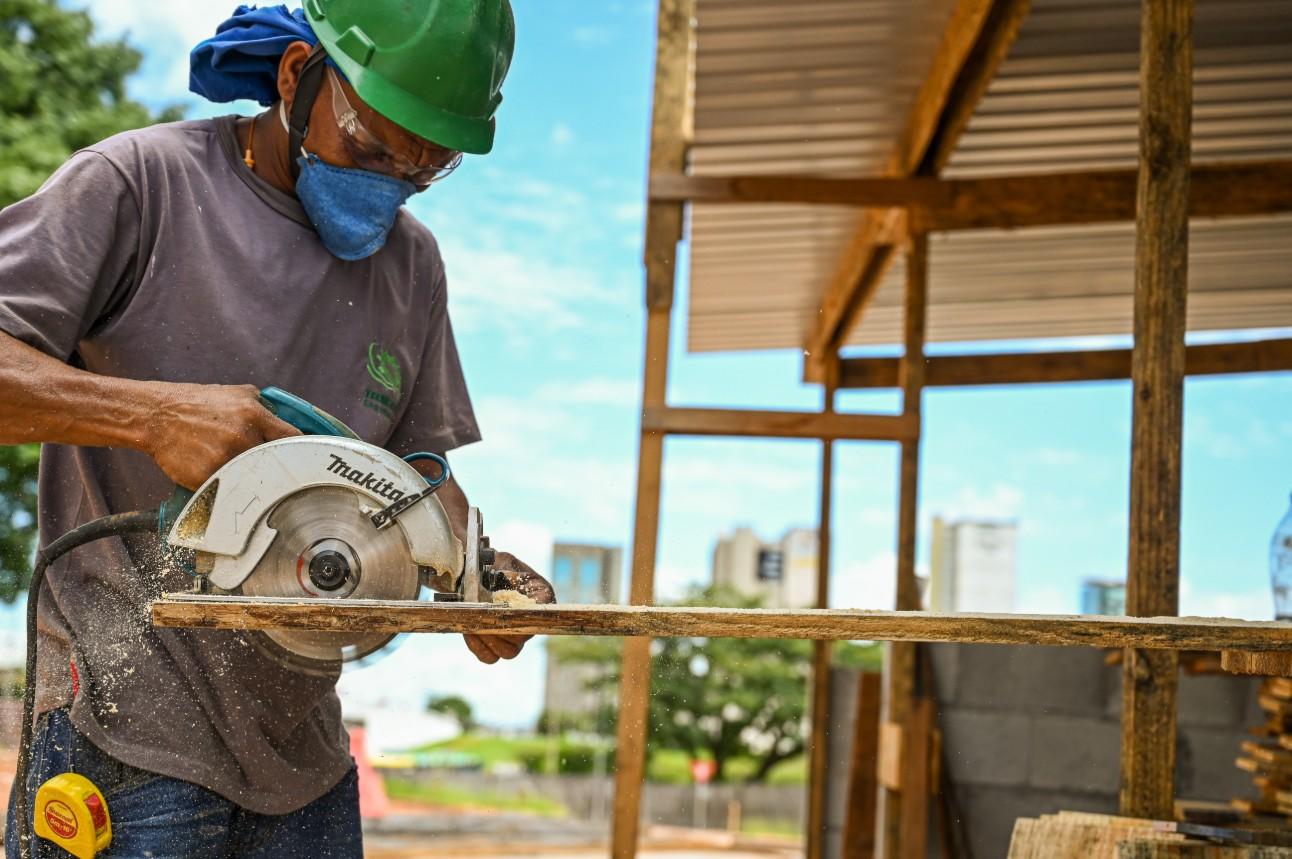 Homem, trabalhador da indústria de construção civil, utiliza máquina de corte em ripa de madeira
