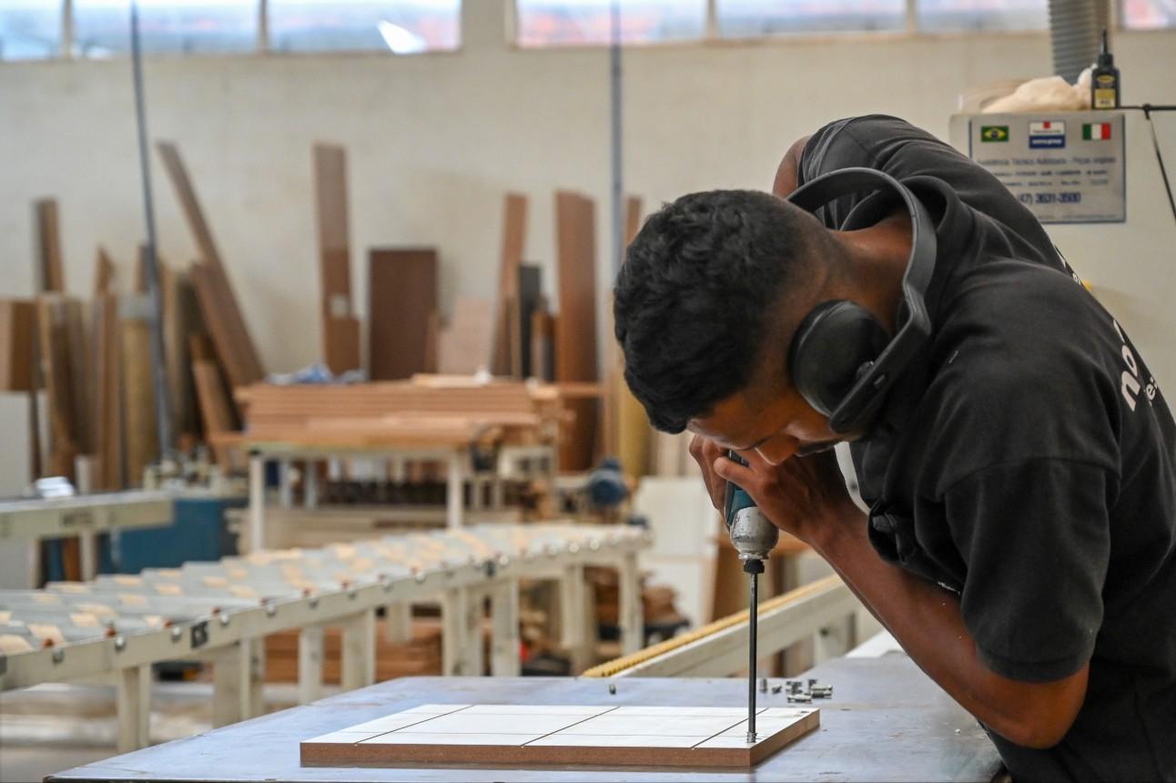 Homem com parafusadeira na mão monta móveis em fábrica