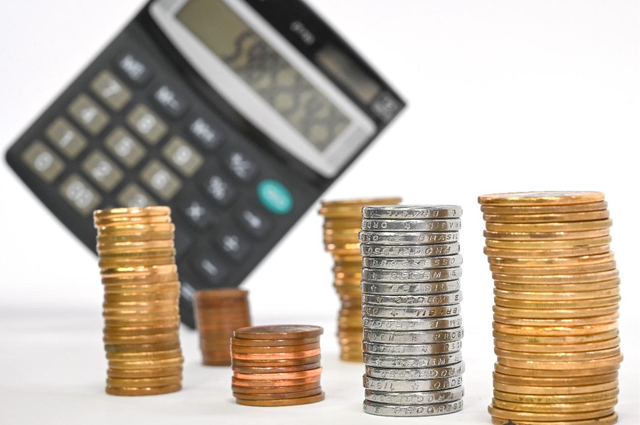 Cédulas e moedas em circulação no Brasil, com uma calculadora ao fundo