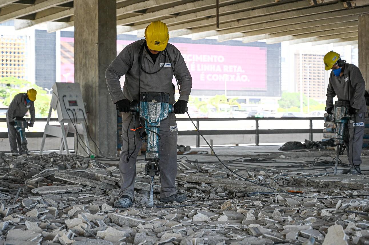Trabalhador da Construção Civil manuseia equipamento de corte de concreto.