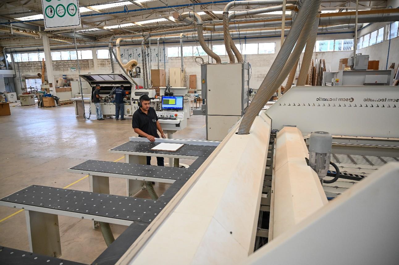 Funcionários trabalhando em uma fábrica de móveis de madeira, com poucos produtos sendo fabricados