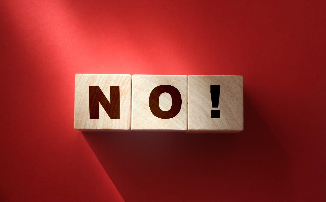Cubos de madeira com texto não em um fundo vermelho. Conceito de resposta negativa. Sem risco, sem violência ou sem conceito de discriminação