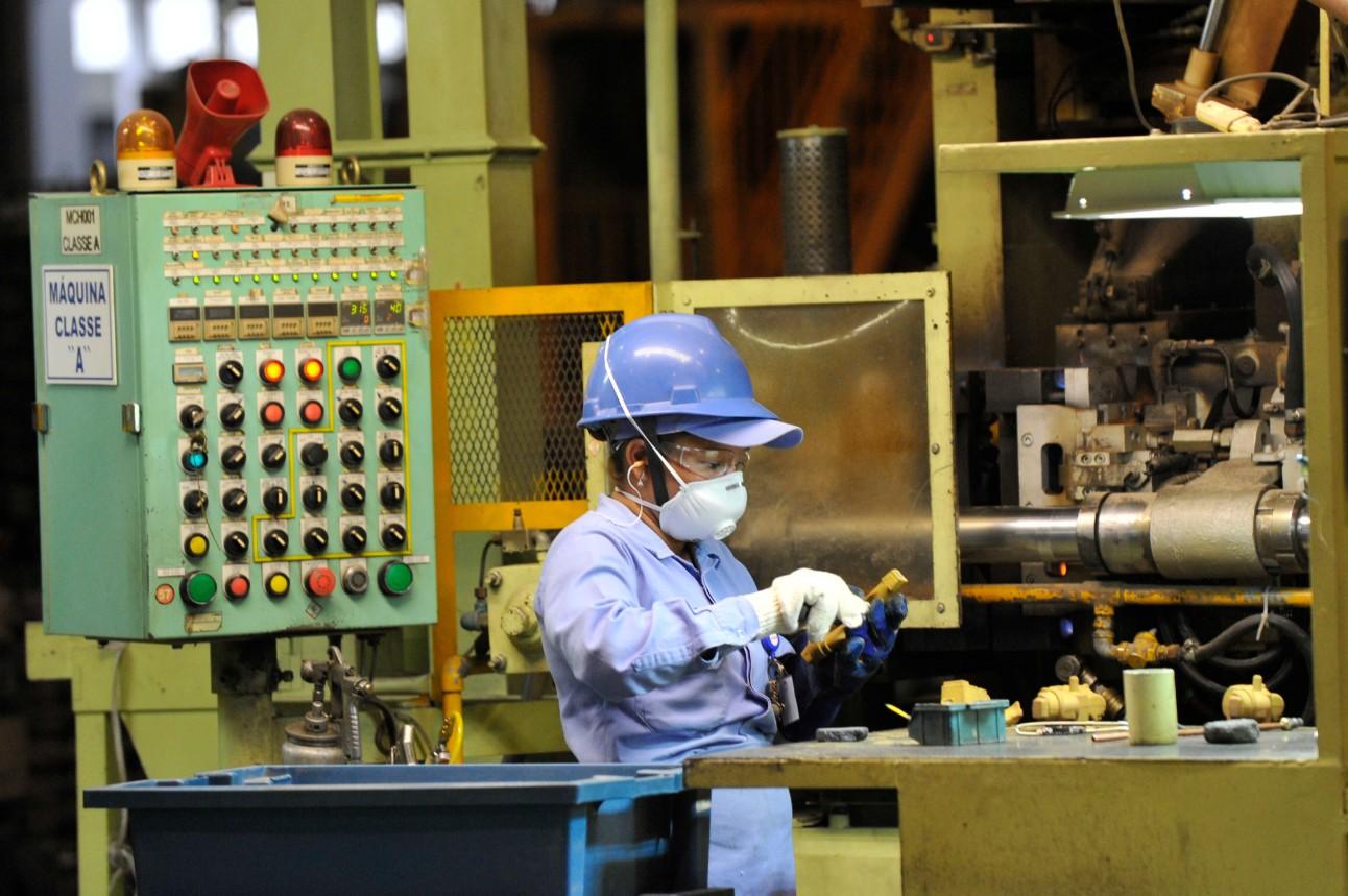 Mulher usando máscara e equipamentos de proteção durante o trabalho em uma fábrica de fundição de peças de motocicletas