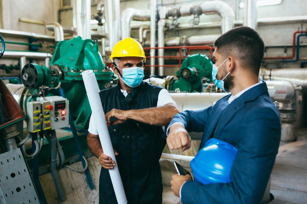 Empresário e trabalhador com máscaras faciais dentro de uma fábrica