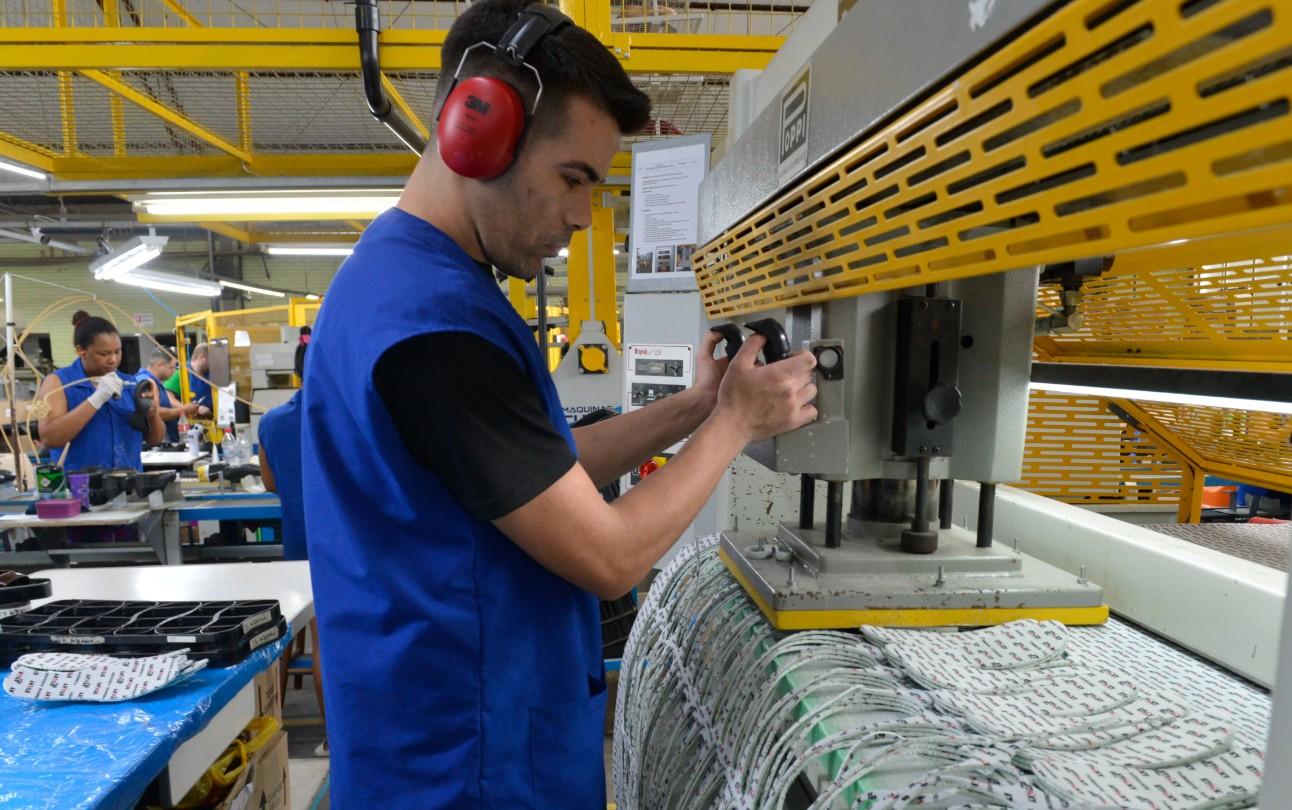 Trabalhador da indústria operando máquina de produção de palmilha fitoterápica