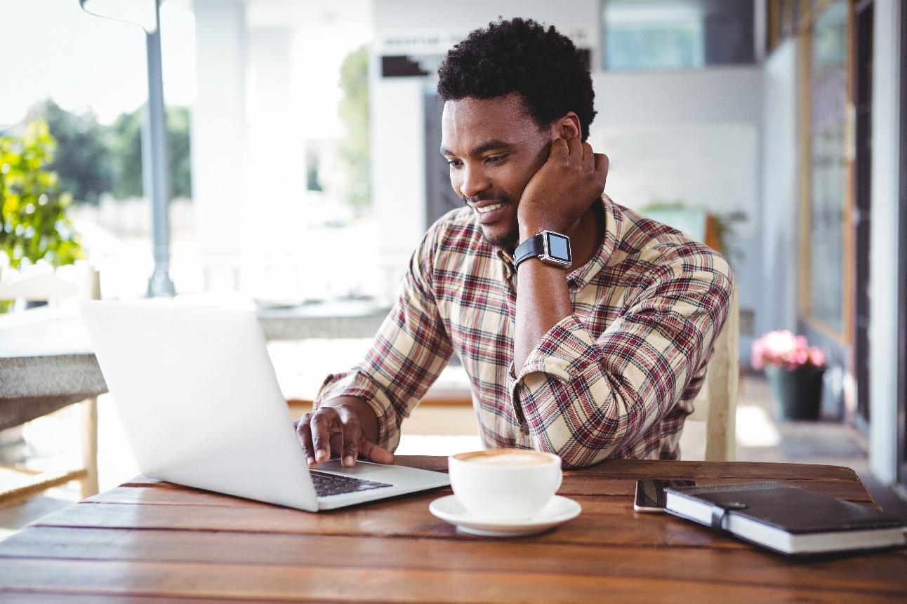 Foto: homem de pele negra, com computador na frente
