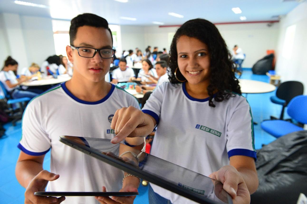 Alunos segurando um tablet dentro da sala de aula