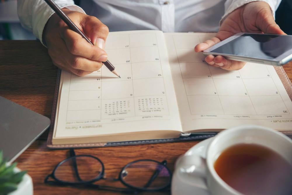 Homem branco, sentando à mesa, com uma xícara de café, faz anotação em calendário