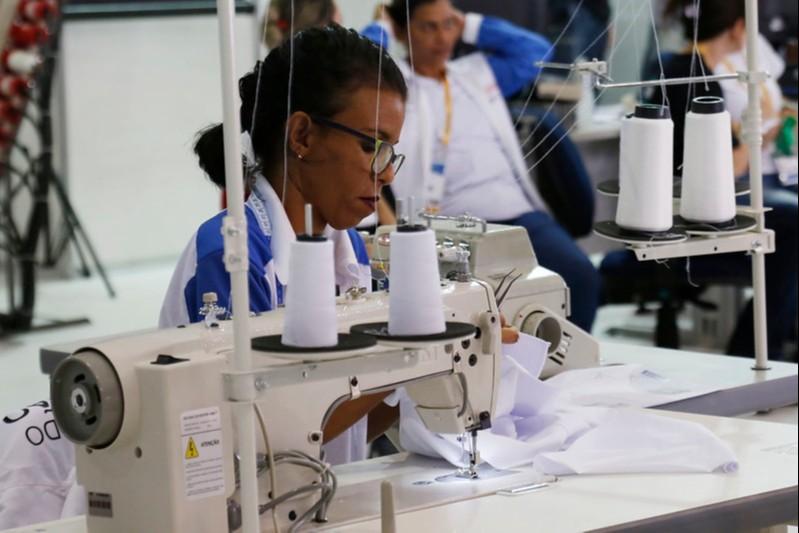 Foto: mulher trabalhando em máquina de costura, a mulher usa óculos e veste uma camisa do SENAI branca e azul.
