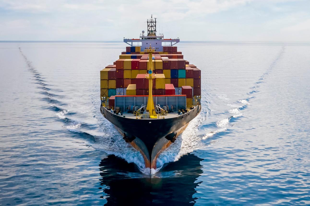 Vista aérea frontal de um navio de carga contêiner carregado viajando sobre o oceano calmo