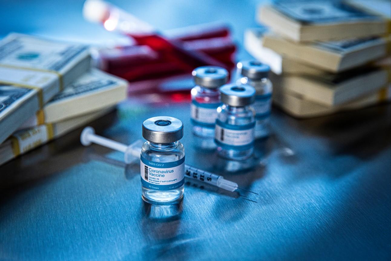 Foto: No fundo, há blocos de cédulas empilhados e tubos com líquido vermelho. Na frente, em foco, há frascos e seringas de uma vacina.