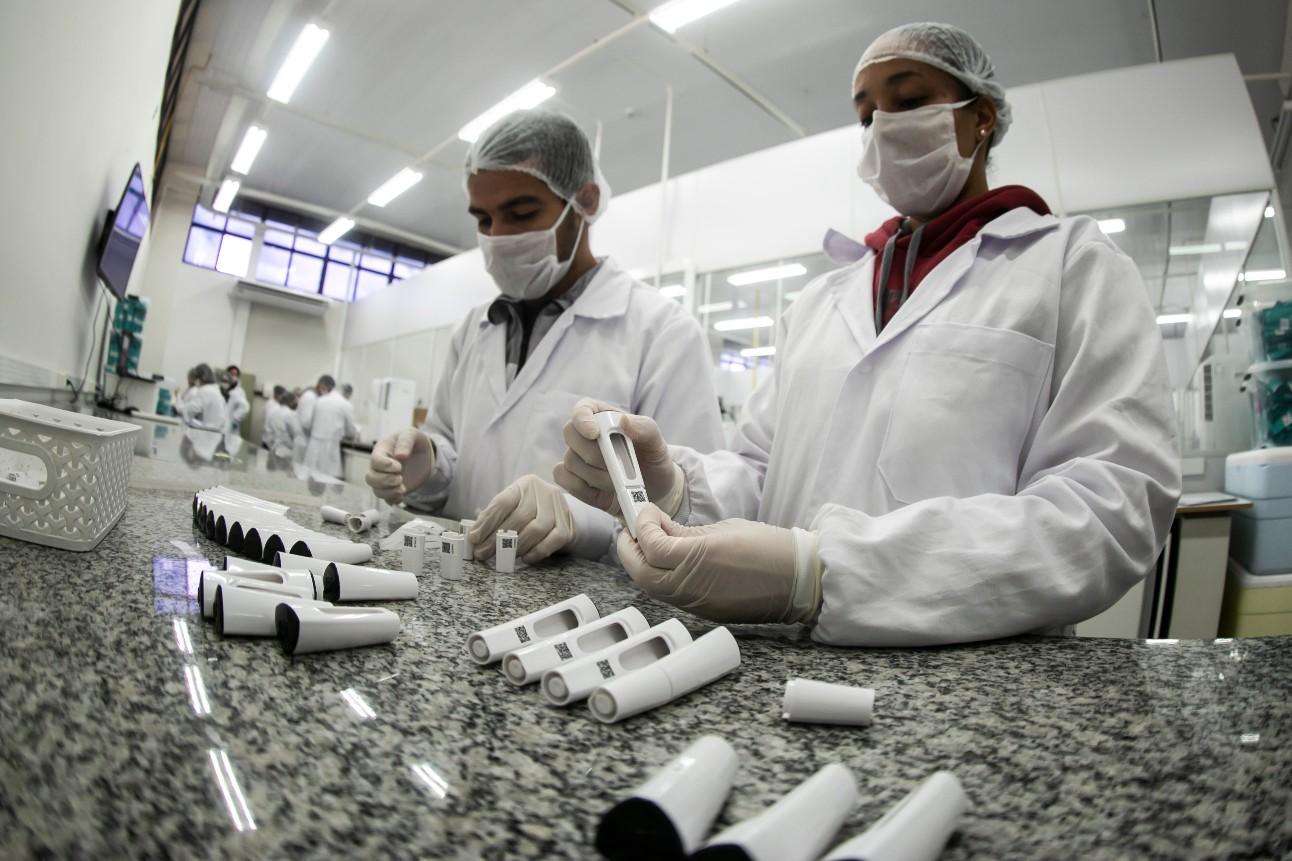 Funcionários de um laboratório, vestidos de jaleco e máscara, manuseiam equipamentos de teste rápido de covid-19
