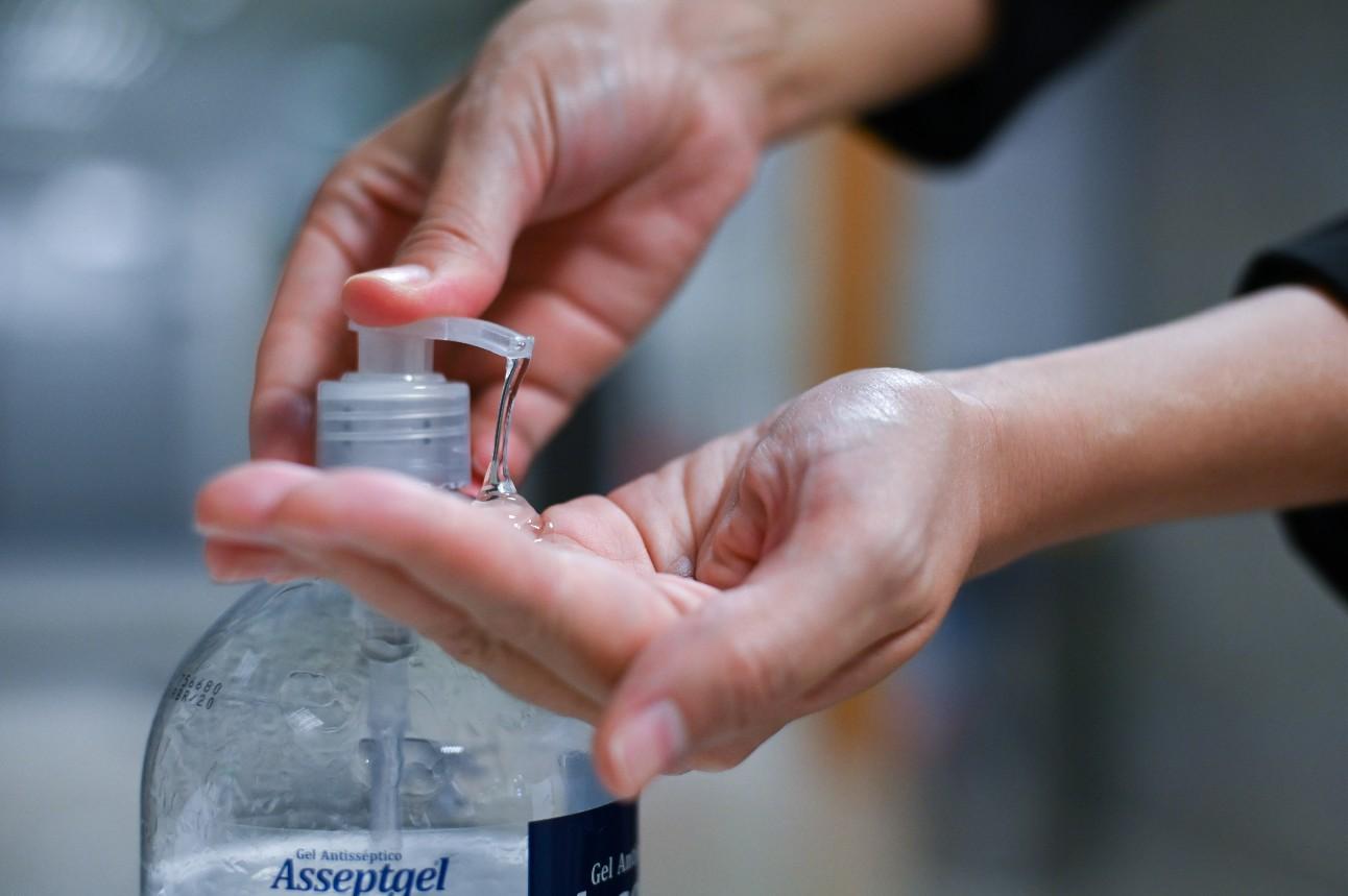 Foto: Mãos pressionado frasco de álcool em gel