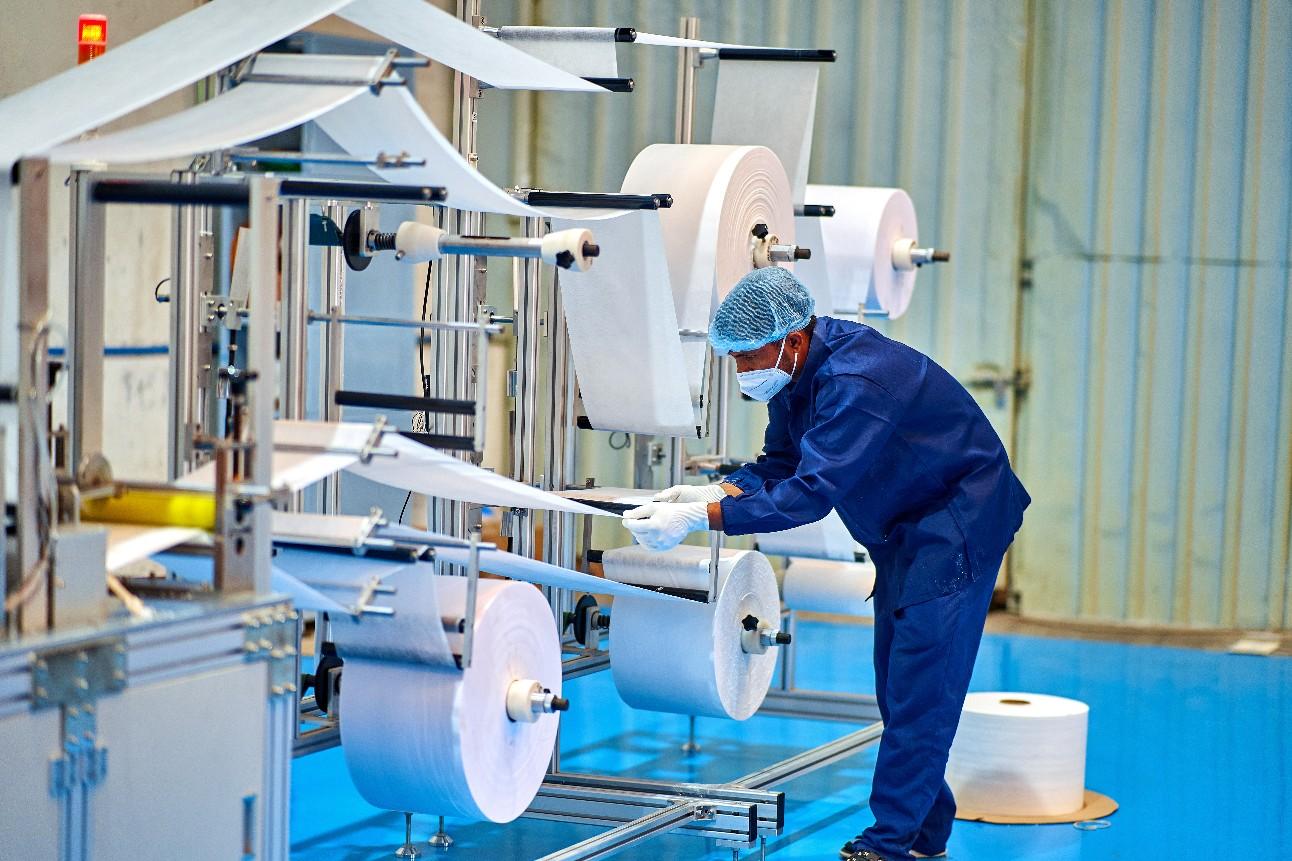 Trabalhador do sexo masculino na fábrica de produção de máscara facial tomando todas as medidas de precaução durante o trabalho