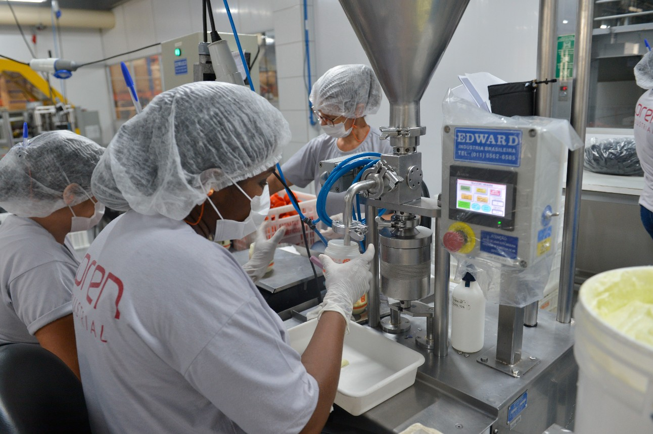 Trabalhadores da indústria utilizando máscaras na fabricação de cosméticos