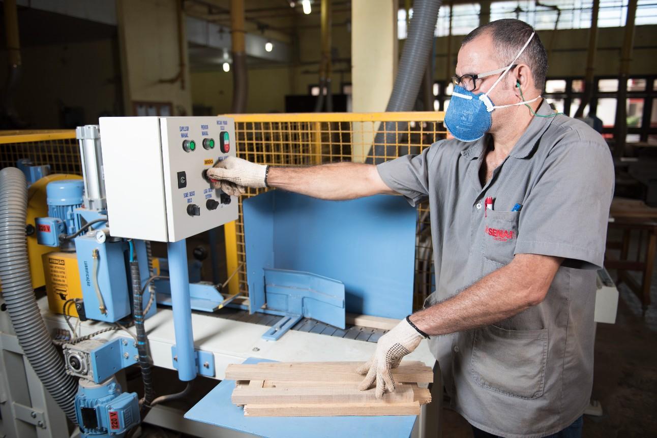 Trabalhador operando máquina do setor de madeira e mobiliário
