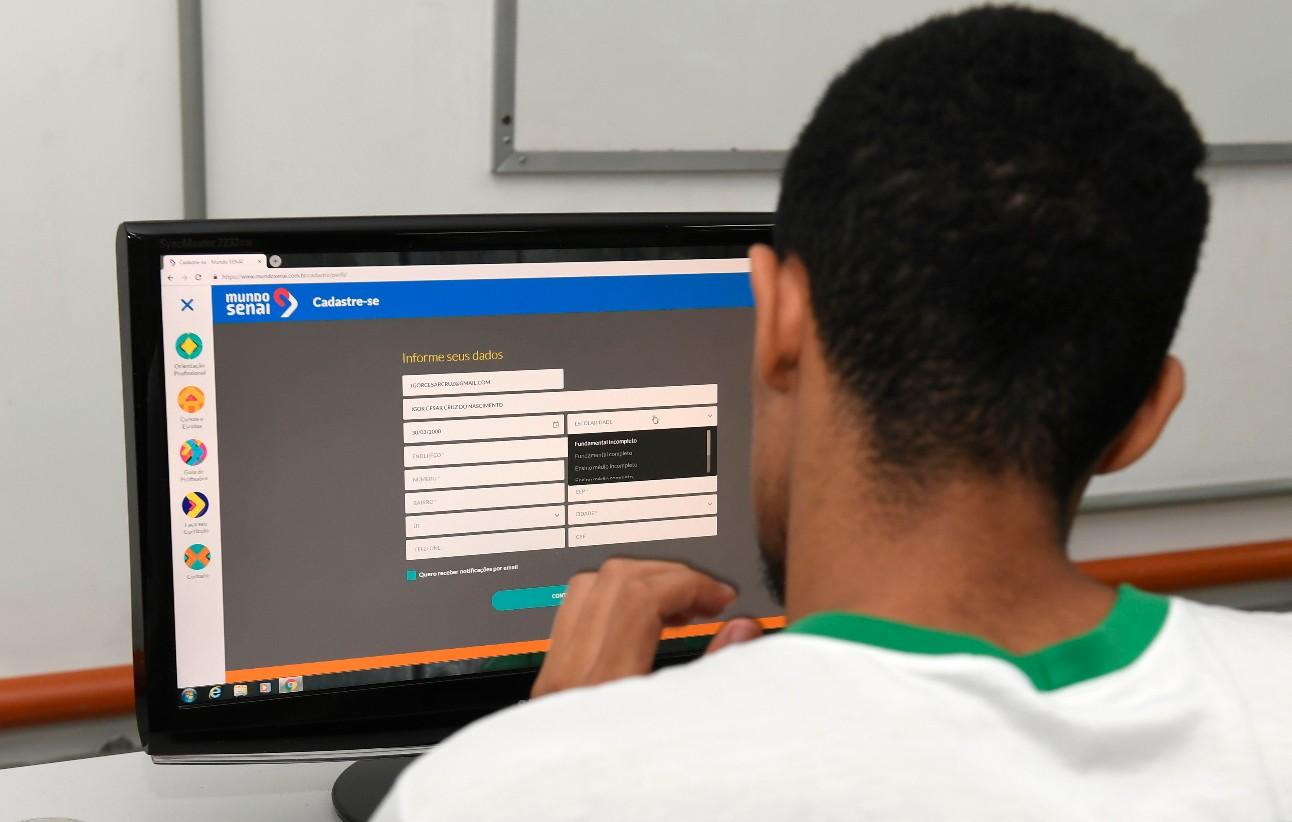 Estudante olhando pra tela do computador aberta na página do Mundo SENAI