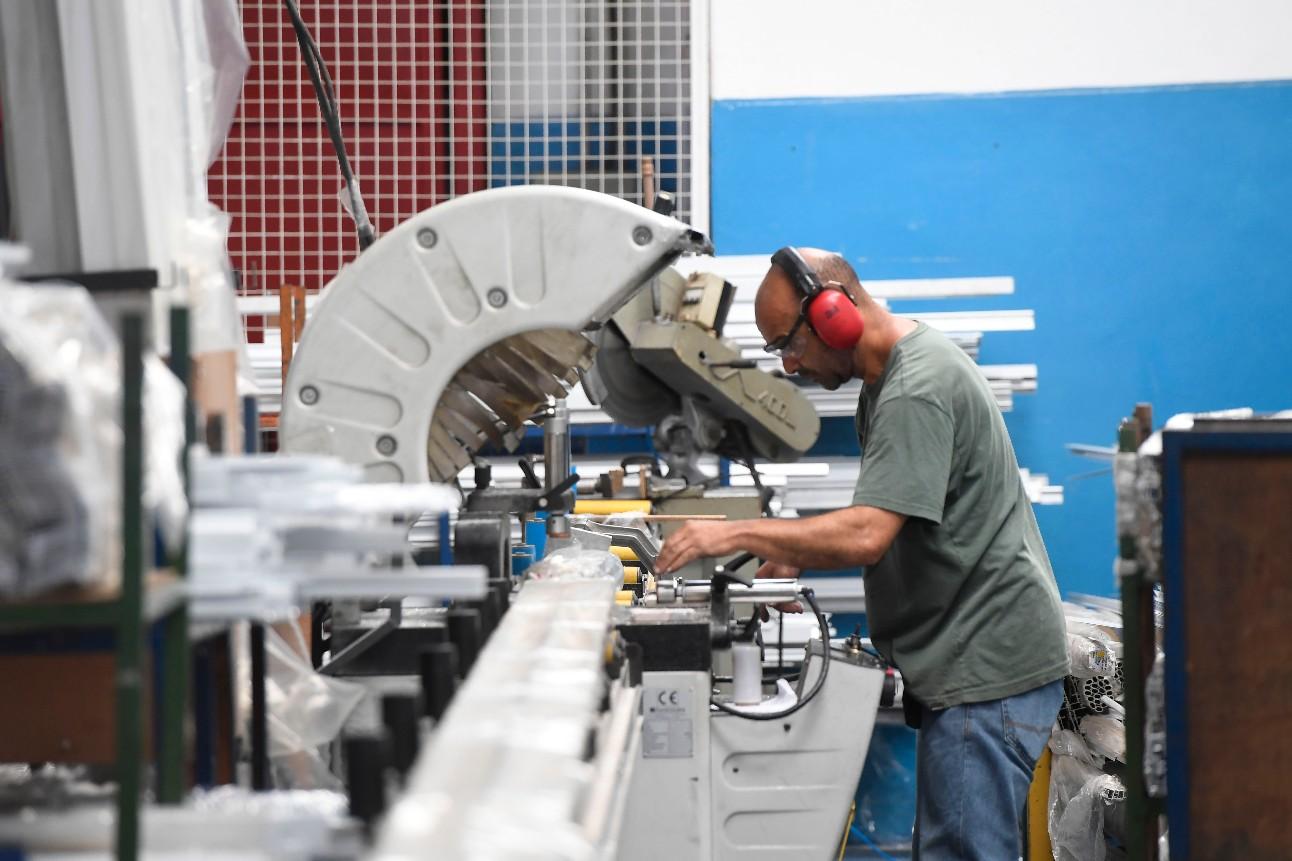 Fotografia mostra homem branco, com protetor de ruídos nos ouvidos operando máquina em uma fábrica de esquadrias