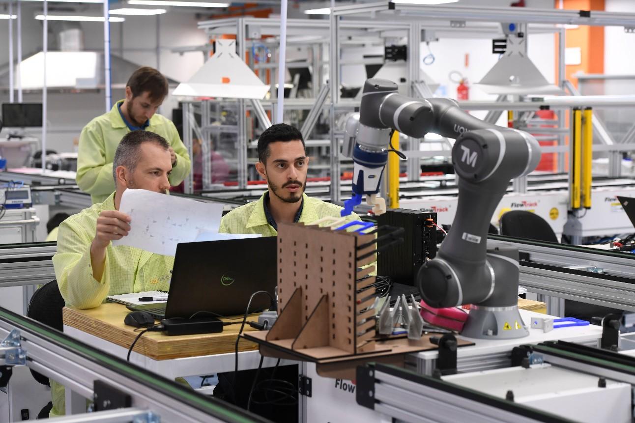 Profissionais em um laboratório de inovação, olhando para um equipamento que funciona por meio de inteligência artificial