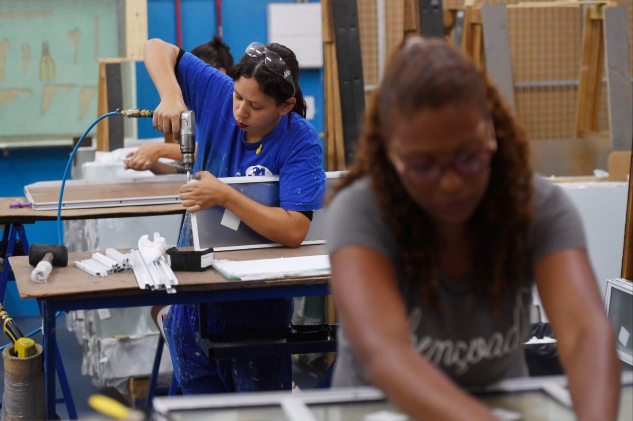 Mulheres trabalhando em fábrica de portas e janelas de alumínio