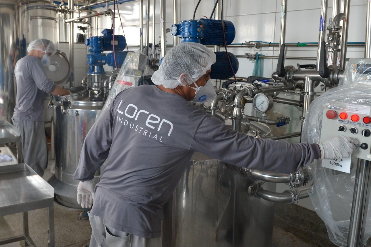Trabalhadores usando equipamento de proteção e operando máquinas dentro de uma indústria de cosméticos
