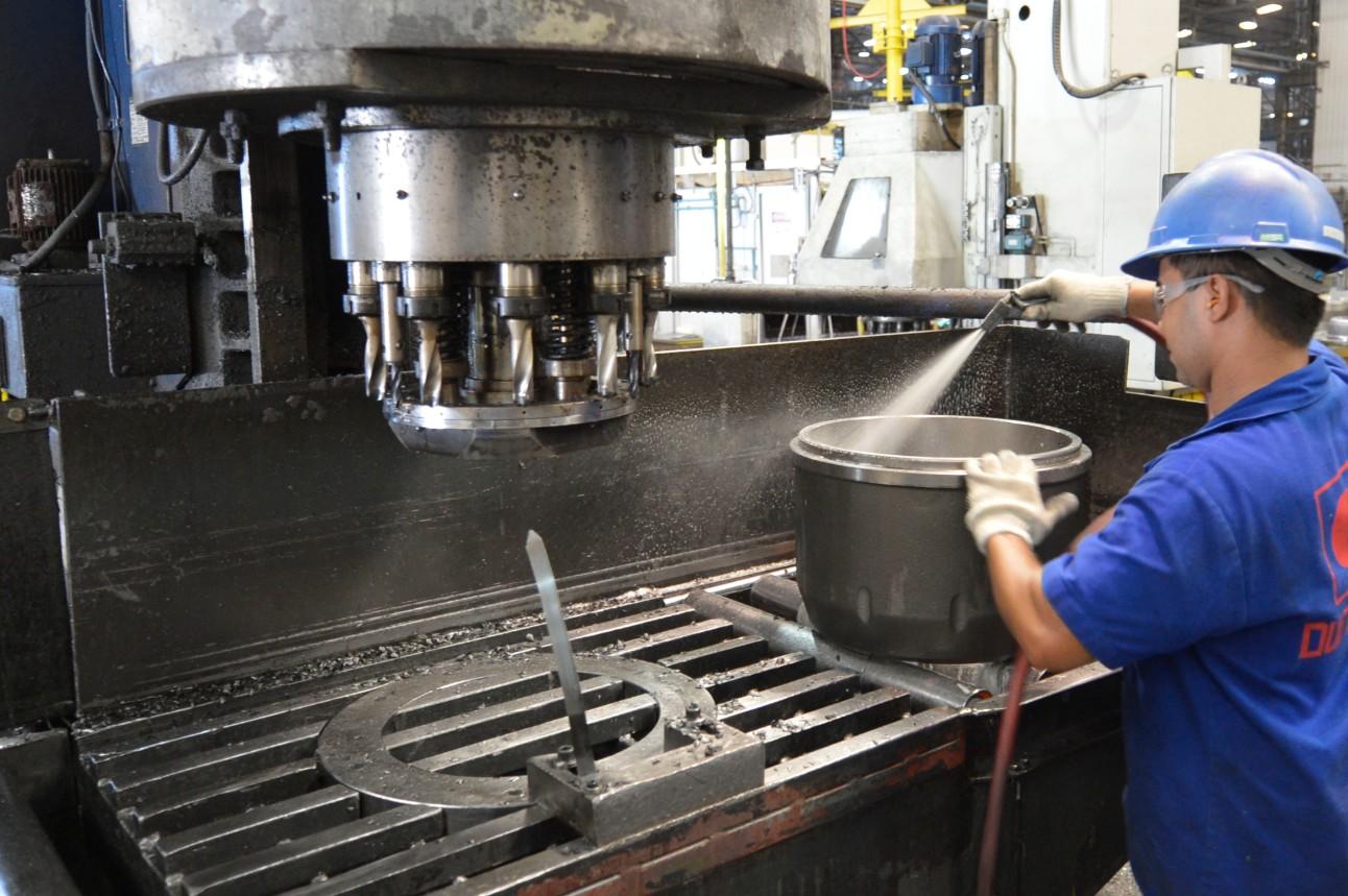 Trabalhador operando máquina durante fabricação de cubos de rodas