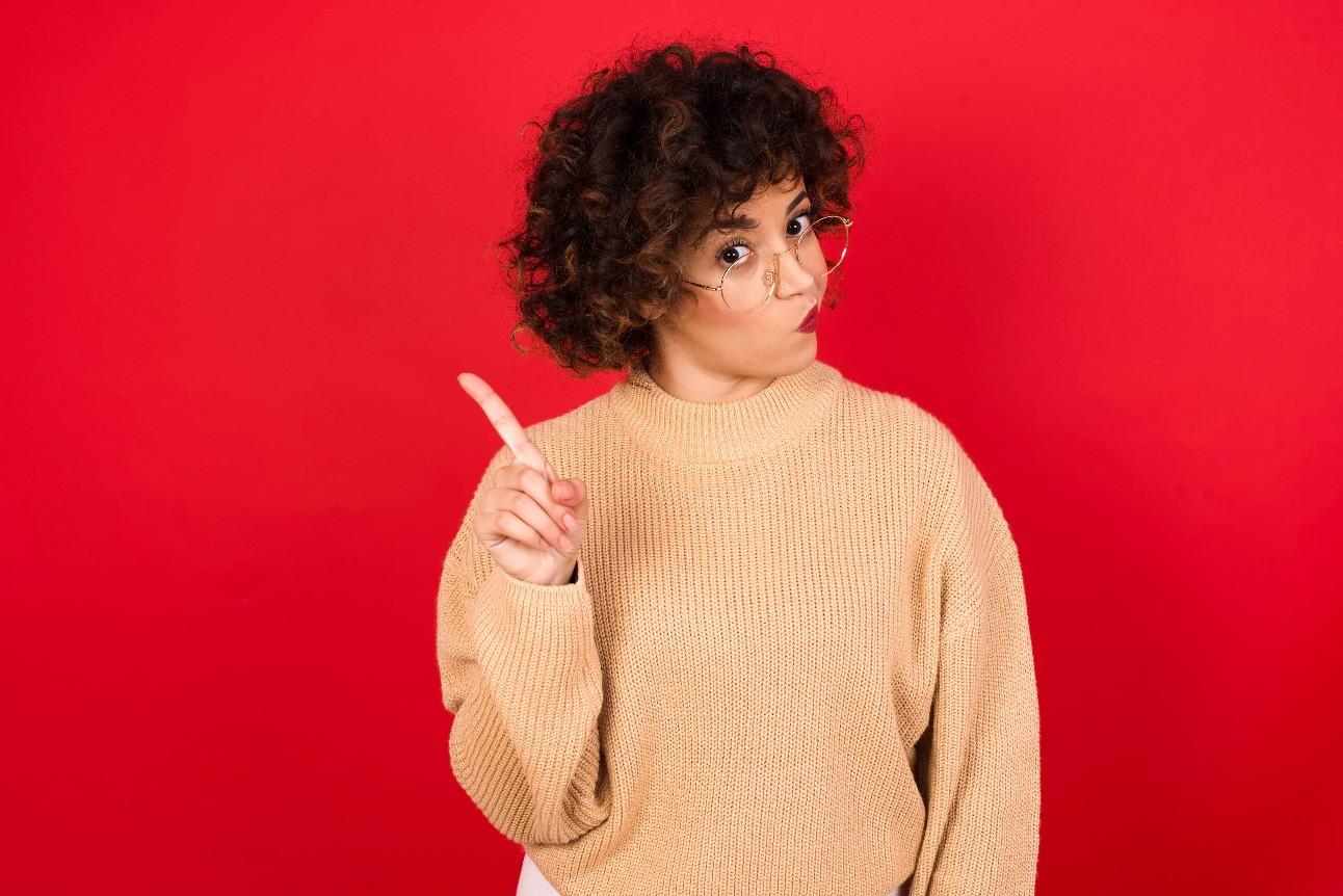 Mulher em pé contra um fundo vermelho, levantando o dedo e dizendo não. Expressões faciais de emoções negativas