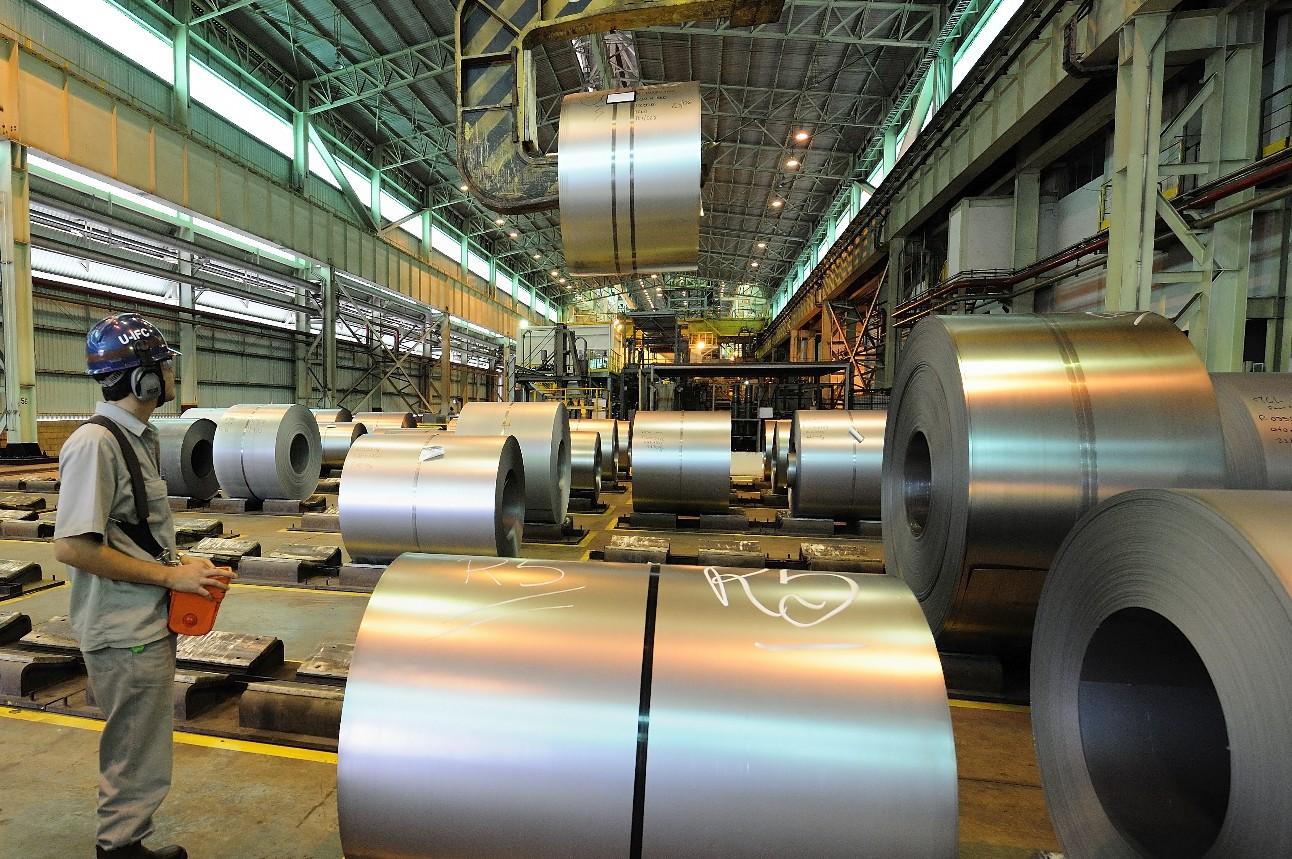Trabalhador operando uma máquina dentro de uma usina siderúrgica