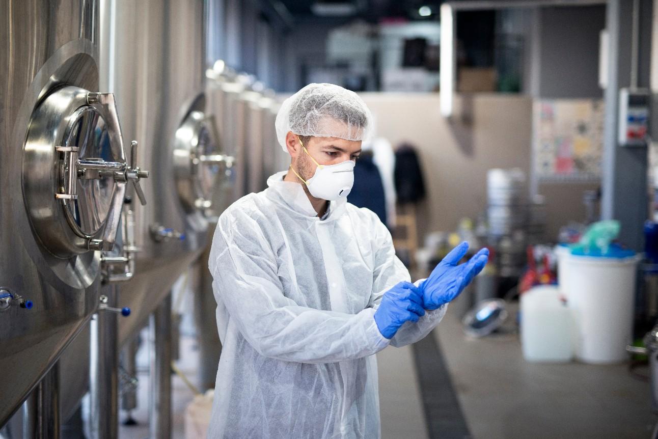 Jovem calçando luvas protetoras de borracha na fábrica