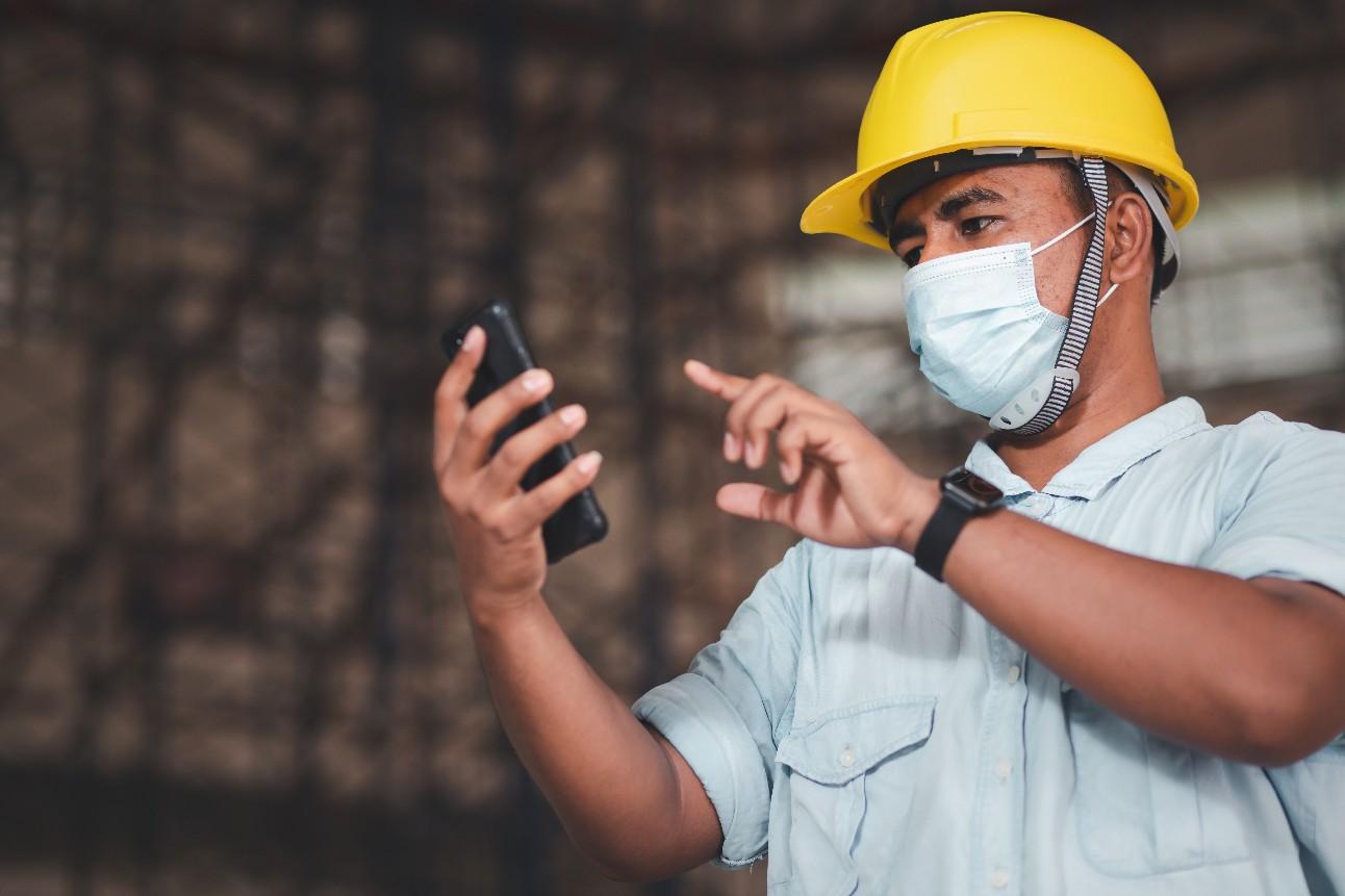 Funcionário da empresa de engenharia usando máscara contra poeira e o vírus Covid-19. Usa um smartphone para controlar o trabalho