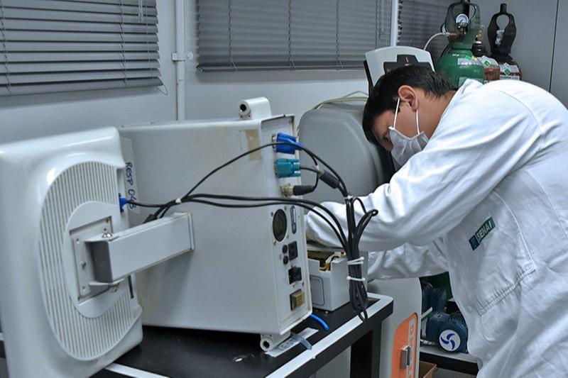 foto: homem de jaleco mexendo em máquina industrial
