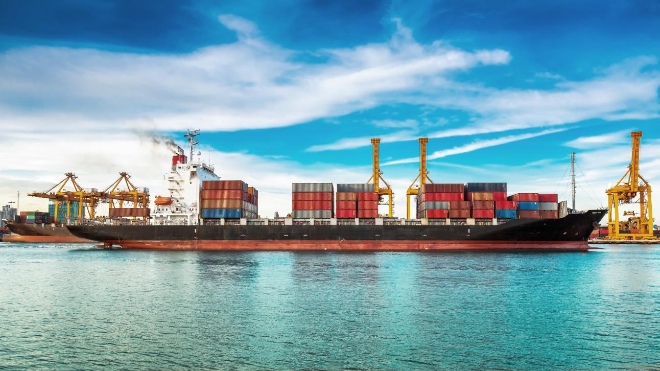 Navio cargueiro atracado em porto, sendo abastecido por conteineres.